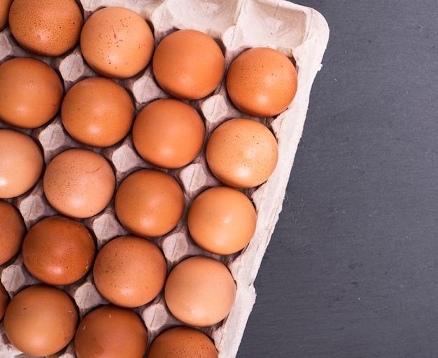 Rohe eier in der eierschale auf papierbehälter