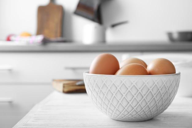 Rohe eier in der schüssel auf küchentisch
