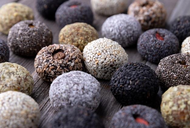 Rohe energie beißt kugeln, die mit natürlichen bestandteilen auf altem rustikalem hölzernem hintergrund vorbereitet werden