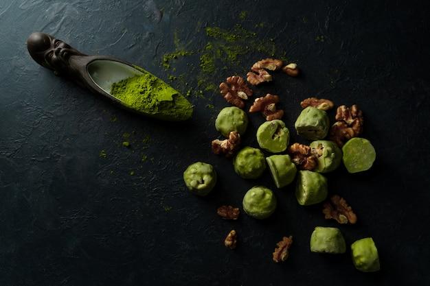 Rohe energiebälle mit matcha teepulver an auf dunklem hintergrund