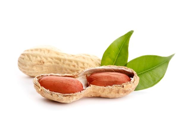 Rohe erdnüsse auf weißem hintergrund mit grünem blatt. gesunder snack ona weißer hintergrund. ansicht von oben. nahaufnahme.
