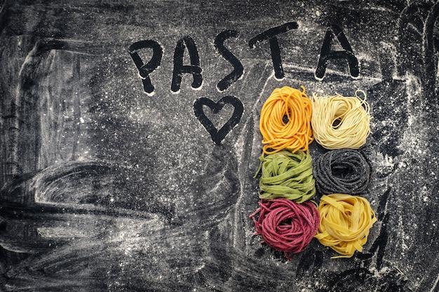 Rohe farbige bandnudeln und spaghettis auf schwarzem hintergrund