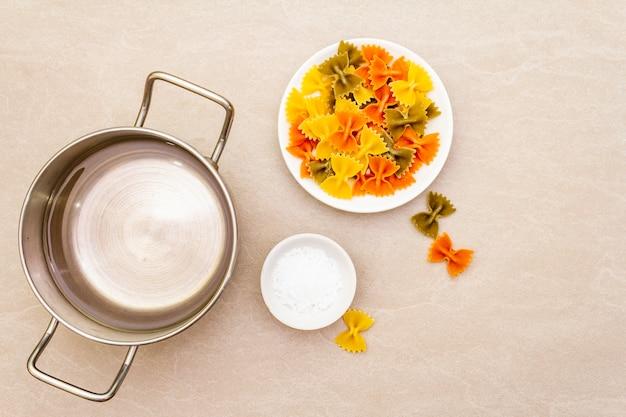 Rohe farfalle mit wasser in topf und salz. mehrfarbige teigwaren in der weißen platte auf steinoberfläche. für kinder sich vorbereiten, draufsicht, abschluss oben