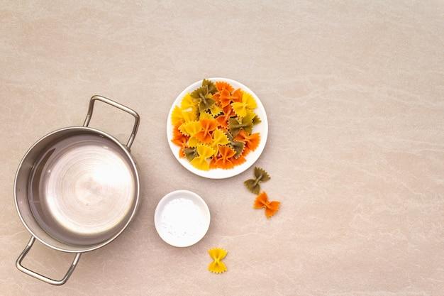 Rohe farfalle mit wasser in topf und salz. mehrfarbige teigwaren in der weißen platte auf steinoberfläche. vorbereiten für kinder, draufsicht, kopienraum