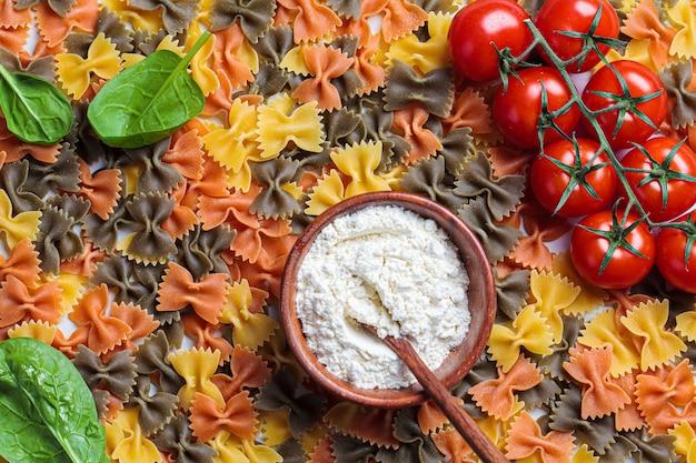 Rohe farfalle-nudeln aus tomaten, spinat und vollkornmehl. Premium Fotos