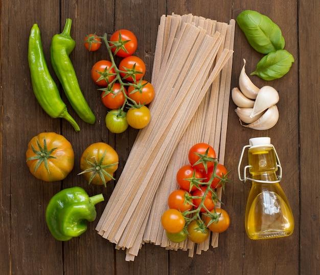 Rohe fettucce nudeln, gemüse und olivenöl auf holz
