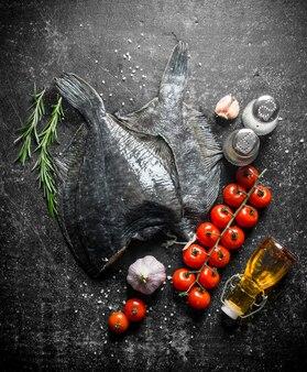 Rohe fischflunder mit kirschtomaten, gewürzen und knoblauch. auf dunkel rustikal