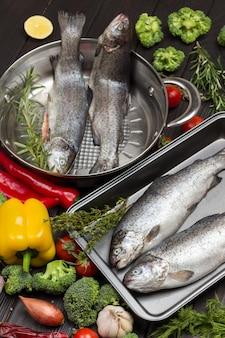 Rohe fischforelle mit gemüse in pfanne und metallschale. blumenkohl, kichererbsen, rosmarin und zitrone, pilze und paprika.