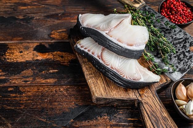 Rohe fischsteaks des blauen hais auf einem schneidebrett mit hackmesser.