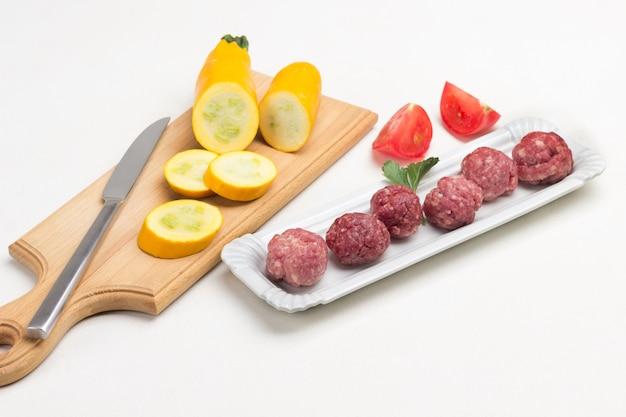 Rohe fleischbällchen auf teller. geschnittene gelbe zucchini und messer auf schneidebrett. weißer hintergrund. ansicht von oben