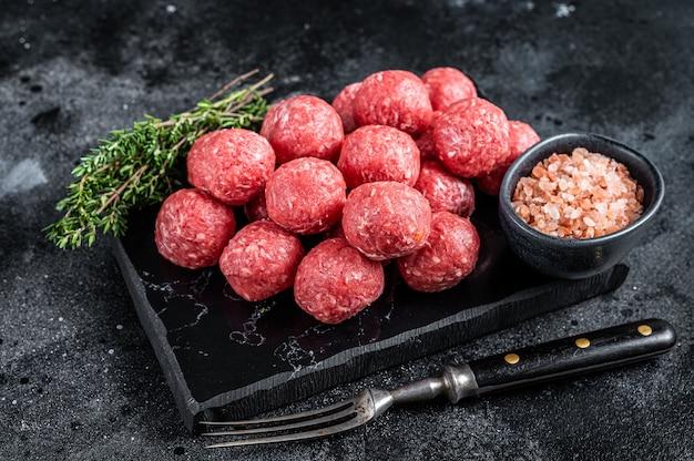 Rohe fleischbällchen aus hackfleisch und schweinefleisch mit thymian. holzhintergrund. draufsicht.