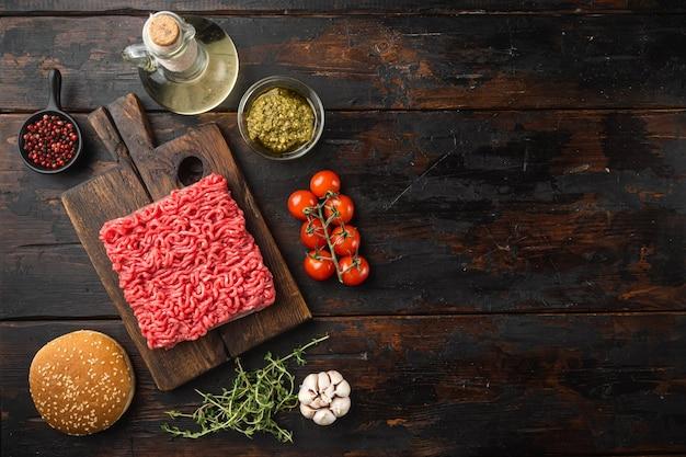 Rohe fleischbällchen burger oder sandwich zutaten mit sesam brötchen gesetzt, auf alten dunklen holztisch, draufsicht flach legen