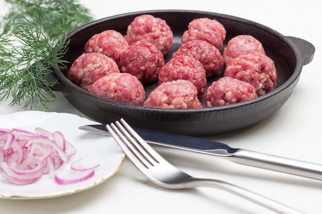 Rohe fleischbällchen in der pfanne. gehackte zwiebel auf teller. dillzweig, messer und gabel auf dem tisch. weißer hintergrund.
