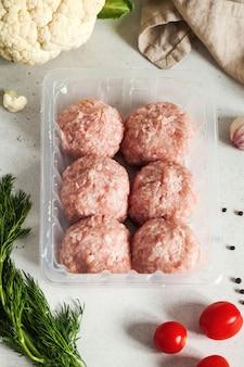 Rohe fleischbällchen und fleischbällchen auf einem plastiksubstrat, umgeben von frischem gemüse, kräutern und gewürzen