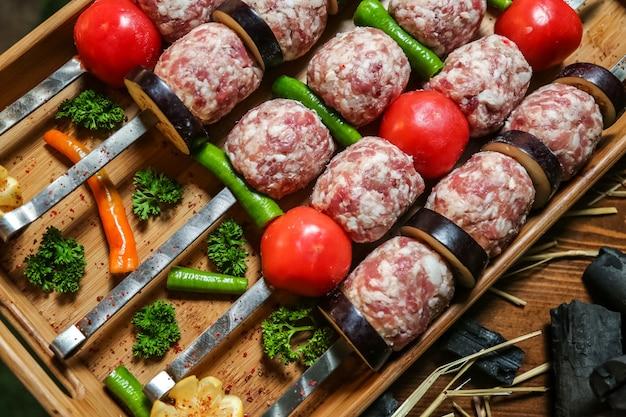 Rohe fleischbällchen und gemüse auf ladestock