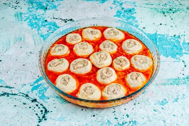 Rohe fleischige teigteigscheiben mit hackfleisch innen mit tomatensauce innen glaspfanne auf blau f