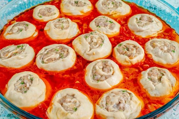Rohe fleischige teigteigscheiben mit hackfleisch innen mit tomatensauce innen glaspfanne auf blau