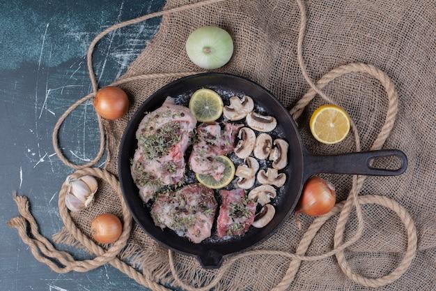 Rohe fleischstücke in schwarzer pfanne mit zwiebeln, knoblauch, zitrone und pilzen.