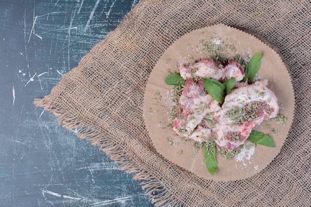 Rohe fleischstücke mit frischen und getrockneten kräutern auf blau.