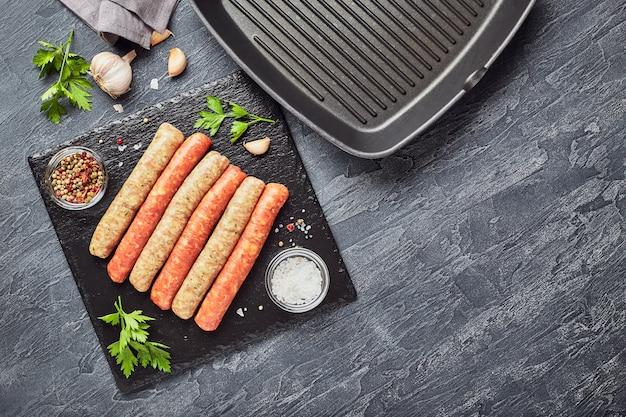 Rohe fleischwürste auf einem schieferbrett mit kräutern und gewürzen und einer quadratischen grillpfanne. sicht von oben.