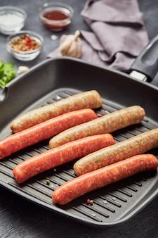 Rohe fleischwürste auf einer quadratischen grillpfanne mit kräutern und gewürzen.