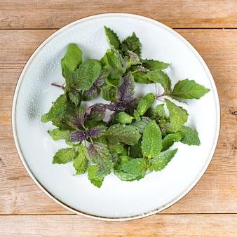 Rohe frische basilikumblätter italienischer salat mit wassertropfen auf grauem teller auf holztisch