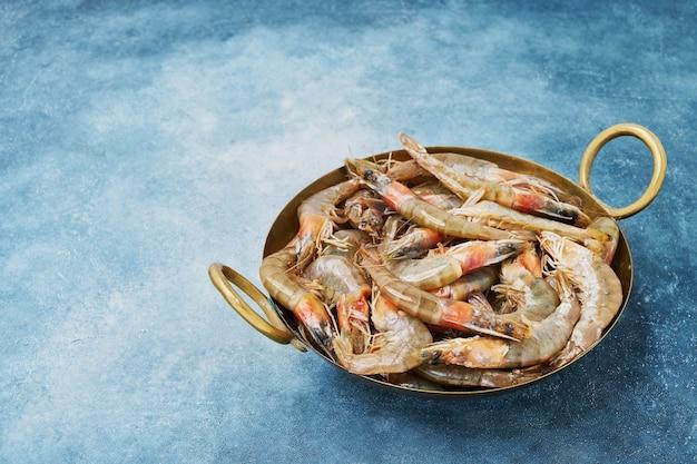 Rohe frische garnelen auf einem weinleseschale über blauem hintergrund. speicherplatz kopieren. konzept für gesunde lebensmittel mit meeresfrüchten.