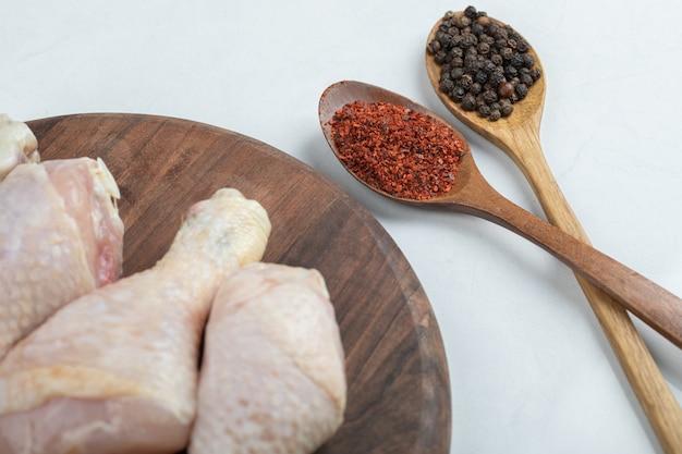 Rohe frische hähnchenschenkel mit zwei löffel paprika.