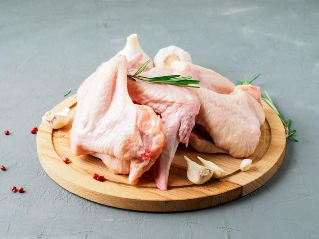 Rohe frische hühnerflügel auf hölzernem brett, grauer konkreter hintergrund, seitenansicht