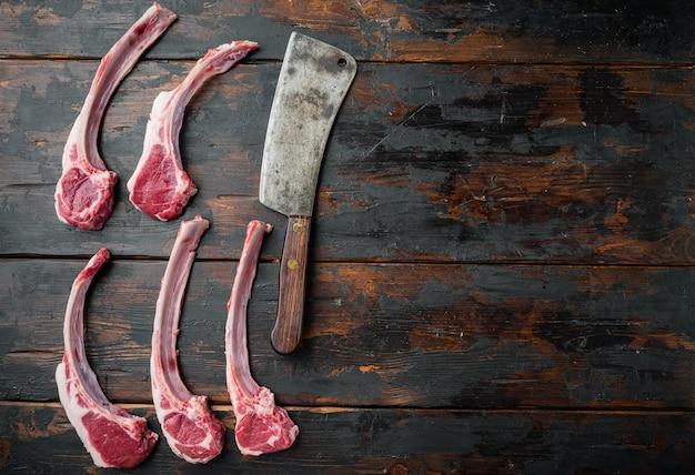 Rohe frische lammrippen, die zum kochen bereit sind, und altes fleischbeilmesser, auf altem dunklem holztisch, draufsicht flach liegen