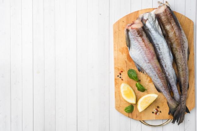 Rohe frische pollockfische auf einem hölzernen brett mit zitrone kopieren raum