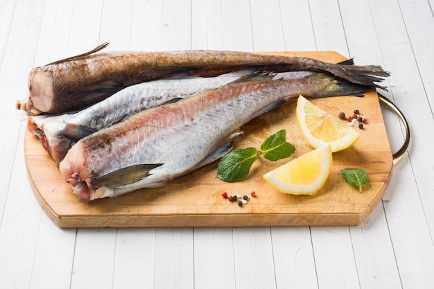 Rohe frische pollockfische auf einem hölzernen brett mit zitrone