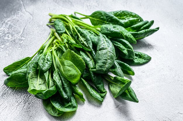 Rohe frische spinatblätter auf einem steintisch. weißer hintergrund. draufsicht.