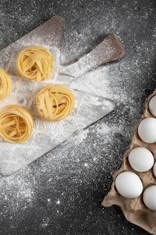 Rohe frische tagliatelle-nester mit mehl auf holzbrett und eiern