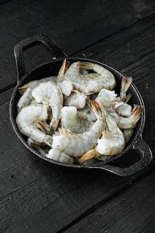 Rohe, frische, ungekochte garnelengarnelen, in einer gusseisernen pfanne, auf schwarzem holzhintergrund