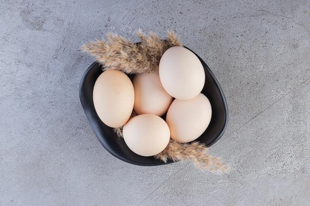 Rohe frische weiße hühnereier, die auf eine steinoberfläche gelegt werden.