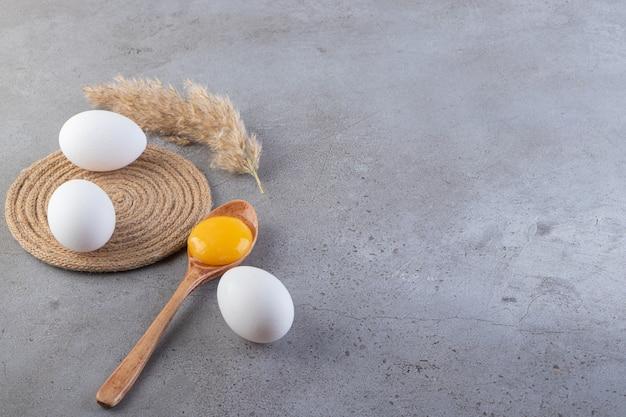 Rohe frische weiße hühnereier, die auf einen steinhintergrund gelegt werden.