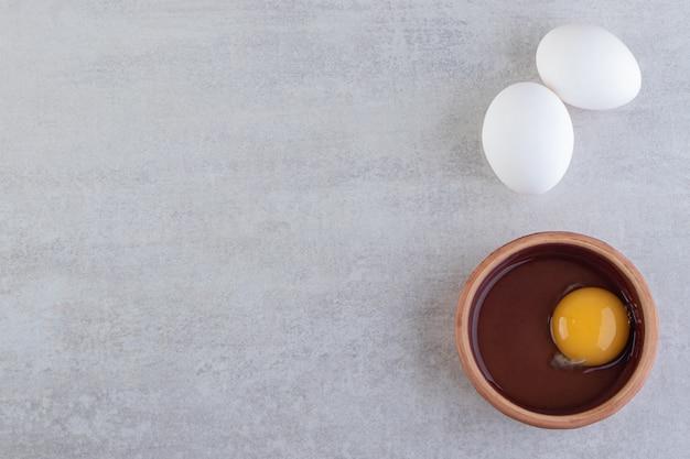 Rohe frische weiße hühnereier, die auf einen steintisch gelegt werden.