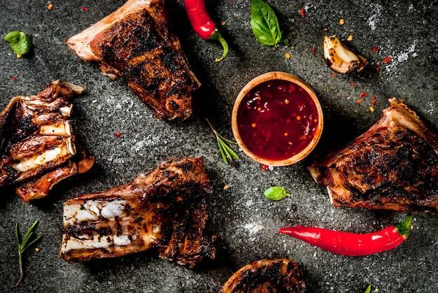 Rohe frischfleisch-, gebratene oder gegrillte lamm- oder rindfleischrippen mit roter tomatensauce, peperoni, knoblauch und gewürzen auf dunklem stein, draufsicht copyspace