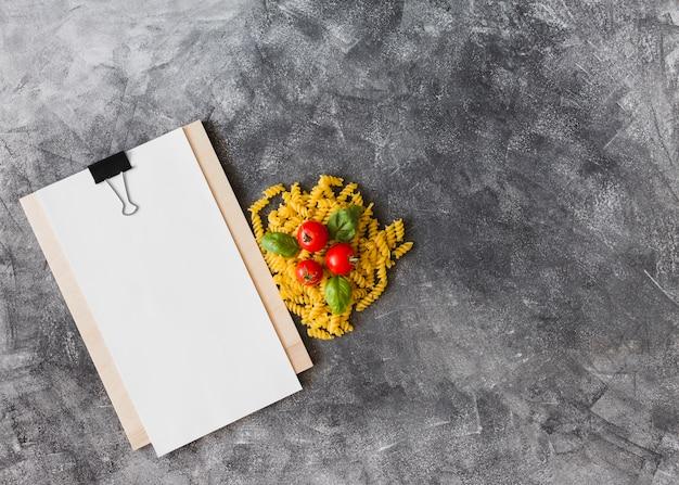 Rohe fusilli mit tomaten und basilikum verlässt mit leerem papier auf klemmbrett gegen strukturierten hintergrund
