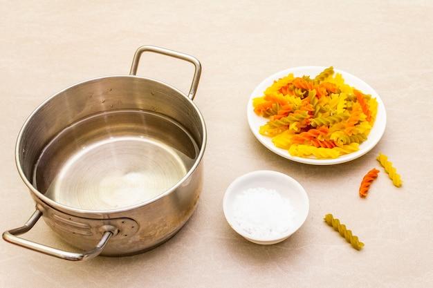 Rohe fuzilli mit wasser in topf und salz. mehrfarbige teigwaren in der weißen platte auf steinoberfläche. vorbereitung für kinder, nahaufnahme.