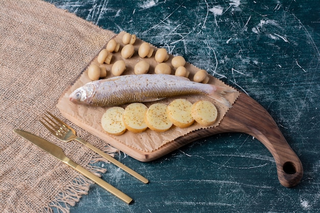 Rohe ganze fische mit oliven und gekochten kartoffelscheiben auf holzbrett.