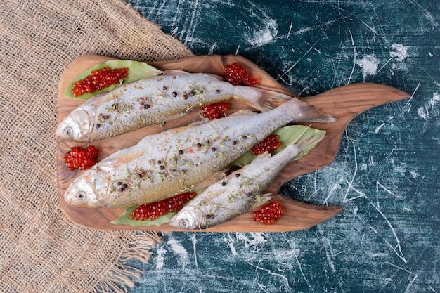 Rohe ganze fische mit rotem kaviar auf holzbrett.