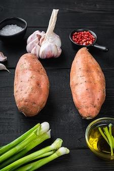 Rohe ganze süßkartoffel mit zutaten, auf schwarzem holzhintergrund.