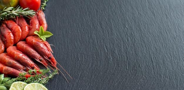 Rohe garnelen mit tomaten, limette und kräutern über dunklem tisch schließen mit kopierraum