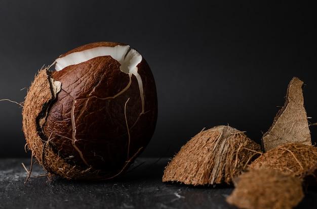Rohe gebrochene kokosnuss auf dunkelheit