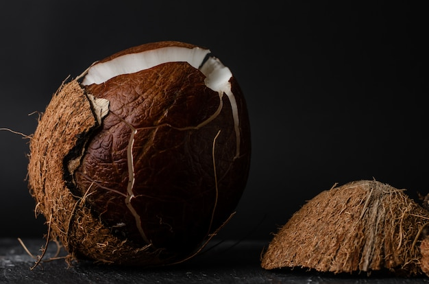 Rohe gebrochene kokosnuss auf dunklem hintergrund.
