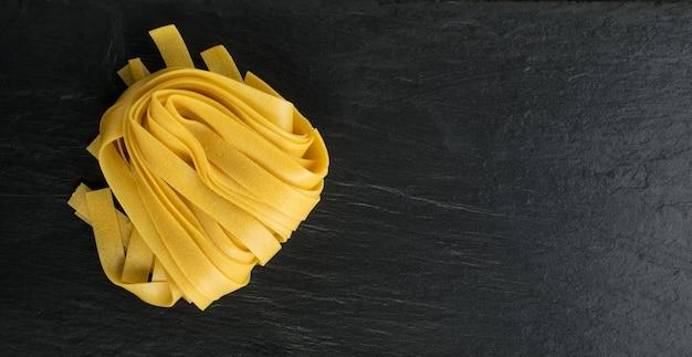 Rohe gelbe italienische pasta fettuccine, fettuccelle oder tagliatelle nahaufnahme. ei hausgemachte trockene bandnudeln, lange gerollte makkaroni oder ungekochte spaghetti draufsicht