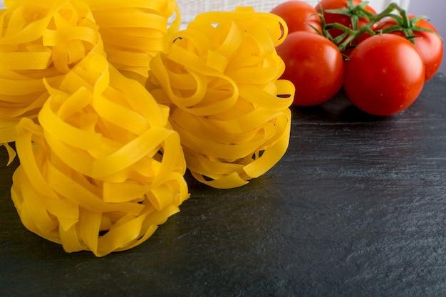 Rohe gelbe italienische pasta fettuccine, fettuccelle oder tagliatelle nahaufnahme. ei hausgemachte trockene bandnudeln, lange gerollte makkaroni oder ungekochte spaghetti