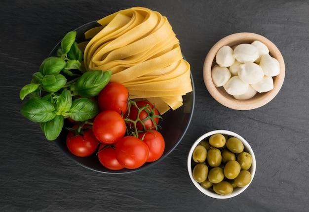 Rohe gelbe italienische pasta pappardelle, fettuccine oder tagliatelle draufsicht. eier hausgemachte nudeln, lange gerollte makkaroni oder ungekochte spaghetti mit oliven, tomaten, basilikum und mozzarella
